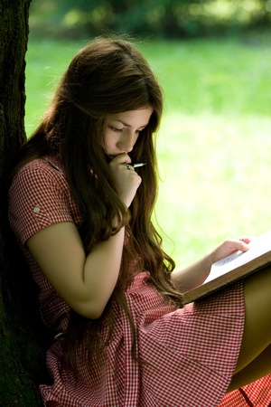 attractive girl with long hair is studying in the park