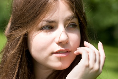 portrait of young woman with clear skin is touching her face by hand in park on green background