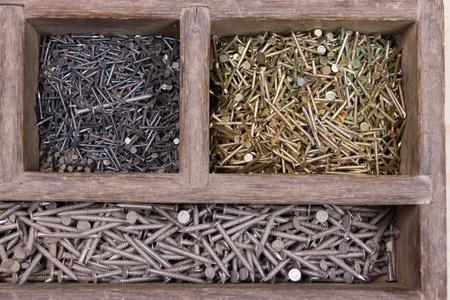 verschiedenfarbige neuen Nägel liegen im Holzkasten in verschiedenen Löchern getrennt