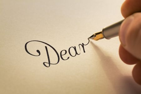 hand is writing calligraphic letter starting with dear using old pen on yellow paper photo