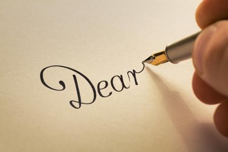 Hand schreibt kalligraphische Buchstaben, beginnend mit lieber mit alten Stift auf gelbem Papier Lizenzfreie Bilder