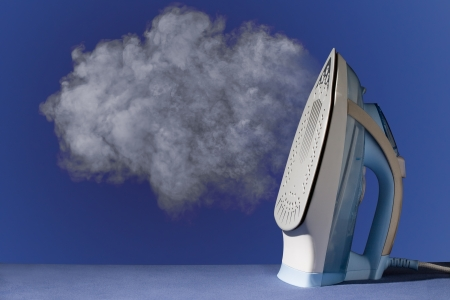steam iron: hot vertical new iron throws cloud of white steam on blue background Stock Photo