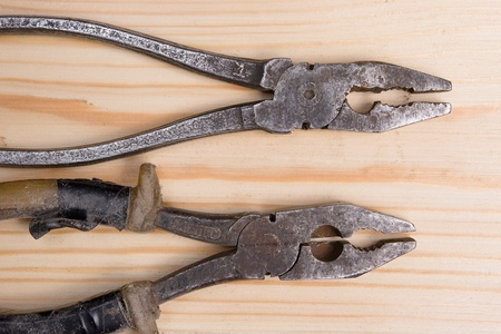hardly: two old hardly used pliers on wooden surface Stock Photo
