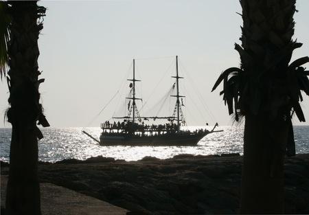 Schiff Konturen am Abend Meer und Palmenstämme am Strand