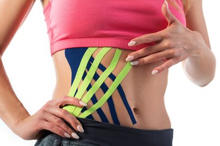 Kinesiо medical tapes on the belly of a young woman