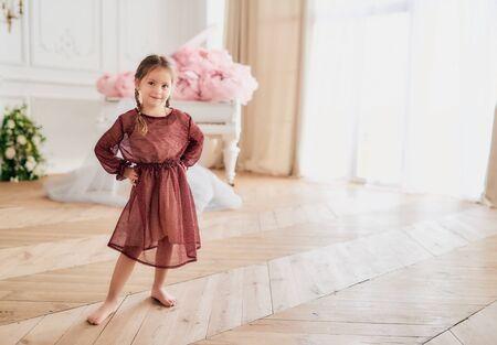 Smiling pretty barefoot girl in festive dress