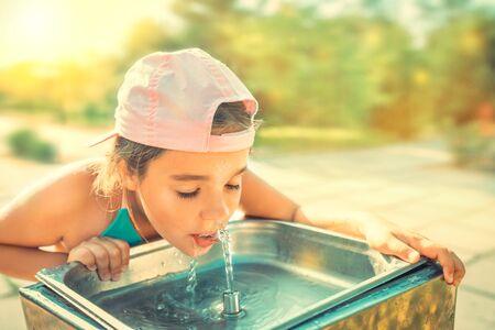 可爱口渴的女孩从饮水槽里喝水