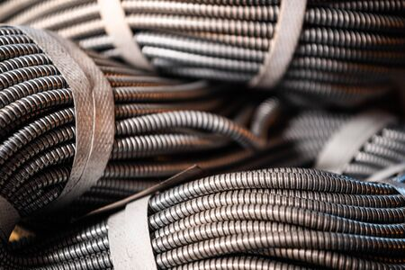 Close-up of a huge golden bundle of metal flexible tubes interconnected in a factory or plant. The concept of modern military and industrial production.