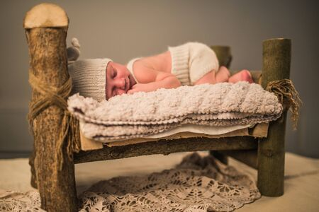 Little newborn sleeping baby lies on the skin on a wooden stool on a gray background. The concept of cute little children in a beautiful surroundings