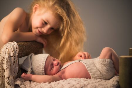 Little cute girl looks at her newborn brother