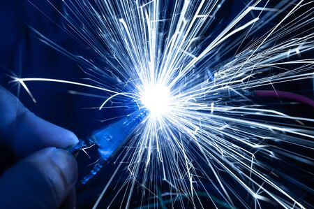 Bright burning sparks fly from incorrectly closed contacts. The concept of danger of electric shock and safety.