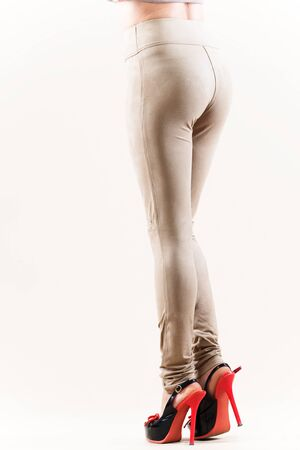 Beautiful slim female legs in beige high heel leggings on a white background. Concept of stylish clothes and slim legs. Place for advertising