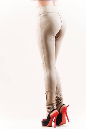 Schöne schlanke weibliche Beine in beige High Heel Leggings auf weißem Hintergrund. Konzept von stilvoller Kleidung und schlanken Beinen. Platz für Werbung Standard-Bild