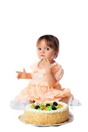 A little girl tries a big cake on her first birthday. Archivio Fotografico - 133285608