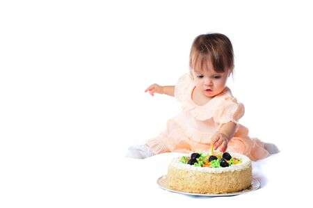 A little girl tries a big cake on her first birthday. Archivio Fotografico - 133285609