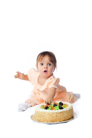 A little girl tries a big cake on her first birthday. Archivio Fotografico - 133285616