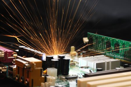 Bright burning sparks fly from the chip of complex electronic equipment. Factory breakdown concept. Breakdown of a new microcircuit