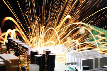 Bright burning sparks fly from the chip of a complex military equipment. The concept of equipment failure at the factory. Breakdown of a new microcircuit