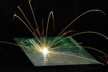 Bright burning sparks fly from the chip of complex electronic equipment on the dark background. Factory welding equipment concept. Creating a new chip. Copyspace