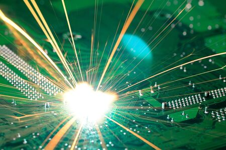 Bright burning sparks fly from the chip of complex electronic equipment. Factory welding equipment concept. Breakdown of a new microcircuit Stock Photo