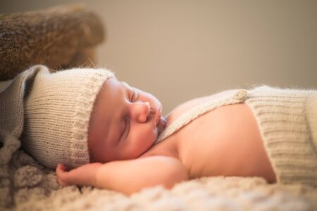 Portrait of a charming newborn little toddler in a knitted hat and shorts sleeping on a cozy bed. Cute of adorable kids concept. Childhood and naive concept