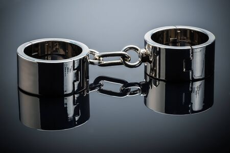 Gold handcuffs lie on a gray metal mirror surface Imagens