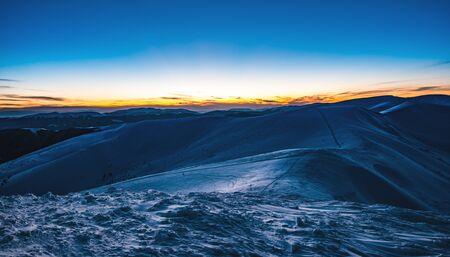 Atemberaubend schöne Aussicht auf die Pisten im Skigebiet nach Sonnenuntergang am späten Abend. Das Konzept des Urlaubs im nördlichen Land an Feiertagen und Neujahrsferien