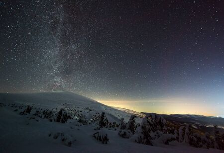 Gwiaździste magiczne niebo z różową mgiełką znajduje się nad zimowym ośrodkiem narciarskim. Pojęcie wakacji na wsi i rozkoszowania się nieskazitelną naturą. Miejsce na tekst