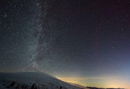 El cielo mágico estrellado con neblina rosa se encuentra sobre la estación de esquí de invierno. El concepto de unas vacaciones en el campo y el disfrute de la naturaleza virgen. Lugar para el texto