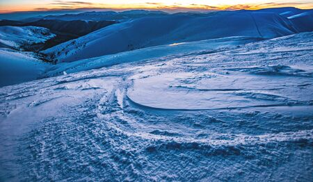 Nice view of a steep ski slope with comfortable tracks in a ski resort on a late winter evening. The concept of extreme sports and recreation in the mountains Stock fotó
