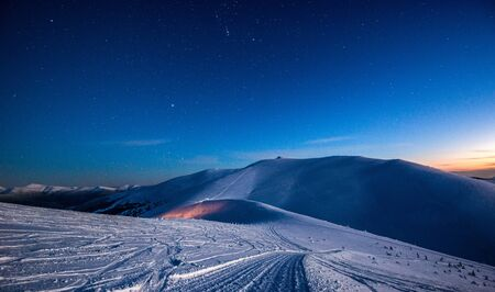 Bewitching view of an empty ski resort under the moonlight at night. The concept of rest in the winter season and breathtaking eco-friendly nature. Copyspace Stock fotó