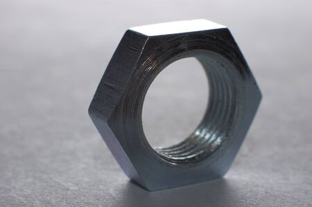 Close-up of one chrome hexagon metal nut stands on a table surface. Manufacturing and hardware repair concept