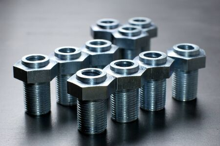 Close-up of several chrome metal bolts with nuts standing on a metal stand next to each other. The concept of repairing fasteners and small production parts