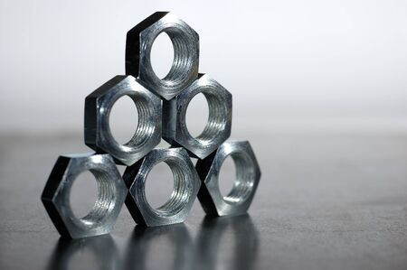 Close-up of a pyramid of five chrome metal nuts in the form of honeycombs next to each other. The concept of repairing fasteners and small production parts. Copyspace