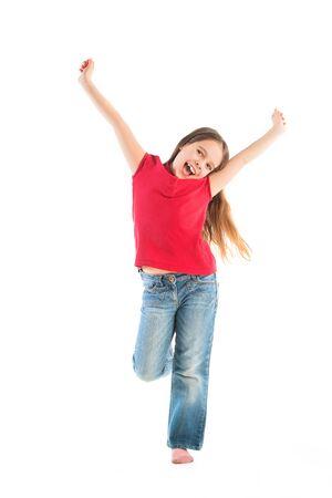 Szczęśliwe dziecko pozuje w ubraniach dla dzieci, stojąc na jednej nodze, z podniesionymi rękami.
