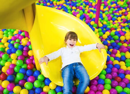 Happy child having fun in the playroom. Girl in children's clothes posing sitting on her knees on a childrens slide