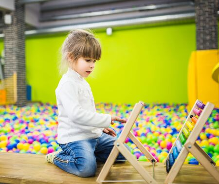 A child in a white sweater and jeans in the playroom is playing with a wood abacus