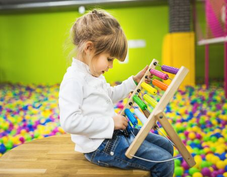 A girl dressed in jeans and a white sweater is playing with a wood abacus toy in the playroom.