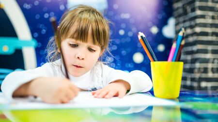 A girl in a white sweater enthusiastically draws with pencils. Portrait photo of a child