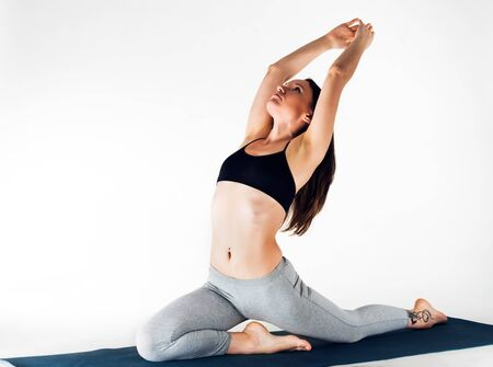 Beautiful graceful young caucasian woman athlete doing a frog exercise while lying on a rug on the floor on a white background. Concept of flexible back and joints. Advertising space Stock Photo
