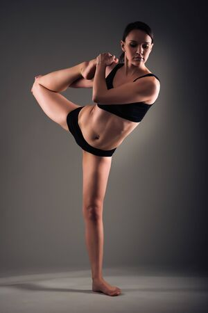 Young athletic woman with beautiful figure in black underwear makes a stretch while standing on one leg on dark background. Concept of a flexible body and healthy joints. Advertising space