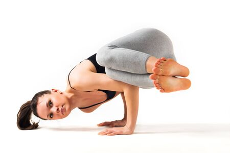 Beautiful young woman yoga teacher doing an advanced asana handstand on a white background. Concept of healthy body joint flexibility. advertising space