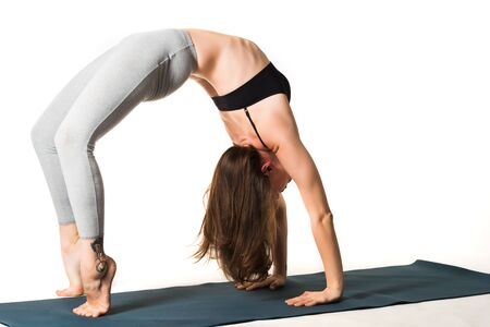 Beautiful slim young girl a yoga lover makes a bridge while standing on the rug. The concept of yoga lovers and professionals. Copyspace