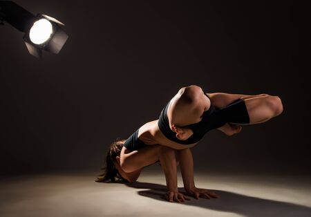 Young woman yoga teacher doing complex asana on hands with a laser in the studio in dark lighting. The concept of body control and flexible and strong body. Place for advertising