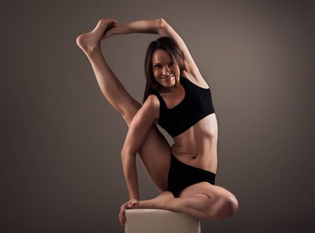 Charming girl athlete brunette in black underwear does yoga asana sitting on a cube on a brown background. Concept of a healthy lifestyle. Advertising space