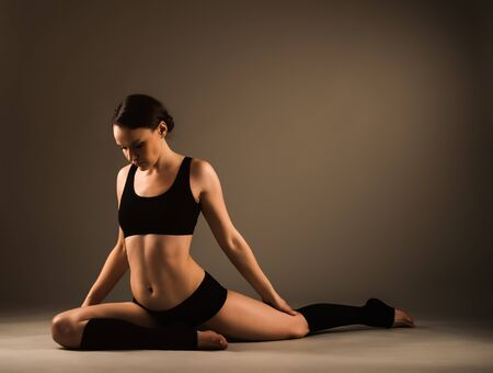 Beautiful young healthy girl in sportswear does a workout for the joints of the legs while sitting on the studio floor in dark lighting. Healthy lifestyle concept. Advertising space Stock Photo
