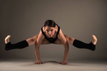 Slim athletic young woman doing a handstand asana yoga studio on a dark background. Flexible and healthy athletic body concept. Advertising space