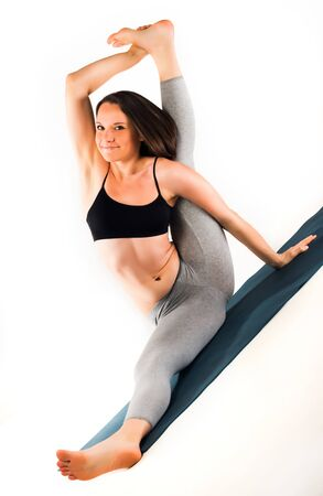 Athletic beautiful young slim woman doing advanced posture on a rug on the floor on a white background. Yoga teacher concept. Advertising space Stock Photo