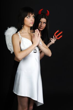 Two girls posing in costumes of an angel and a demon. A woman in a white dress holds hands in front of face. Dark background 免版税图像