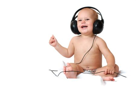 Little one year old boy listens to music in big headphones and smiles on an isolated white background Фото со стока